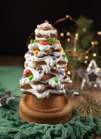 Baked gingerbread christmas tree on wooden background. Close-up. With icing sugar as snow. Selfmade gift for xmas. Homemade food for winter holidays. Cookies and cake. Фото со стока - 150296990