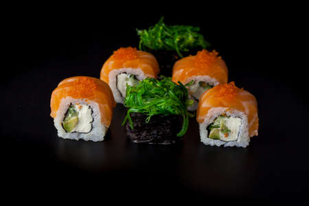 Salmon sushi set. Sushi roll Philadelphia with red fish, salmon, red caviar. Roll with soft avocado and cream cheese under a layer of massago caviar. Classic sushi on a black background. Food.