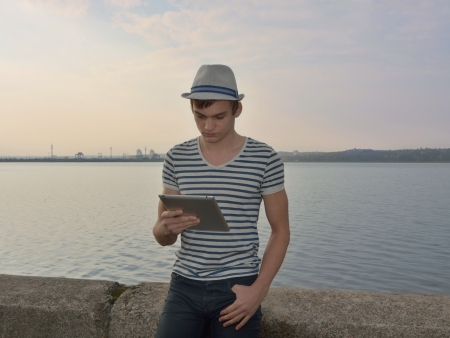 The young man is looking on a tablet in front of sea photo