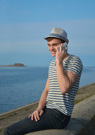 Young man speaking on a cell phone and smiling photo