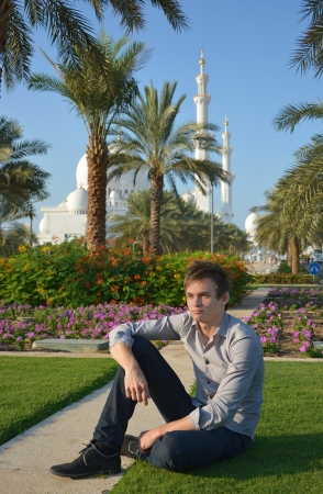 Young man sitting in a park near the Sheikh Zayed Mosque in Abu Dhabi, UAE  photo