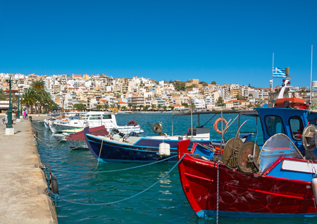 Greek fishing boats in Sitia  Traditional Greek boats in red and blue colors bobs on the waves on a clear sunny day  Port of Sitia, Crete  photo