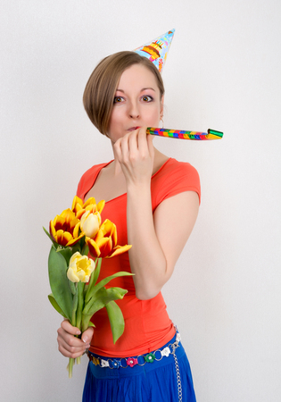 Woman celebrating birthday with tulips, streamer and party hat in front of a white  photo