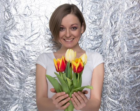 Young woman with a bouquet of tulips in front a silver A smiling girl in a blue skirt and white t-shirt photo