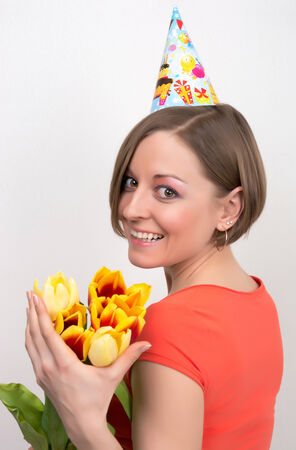 Woman celebrating birthday with tulips, party hat in front isolated on white  photo