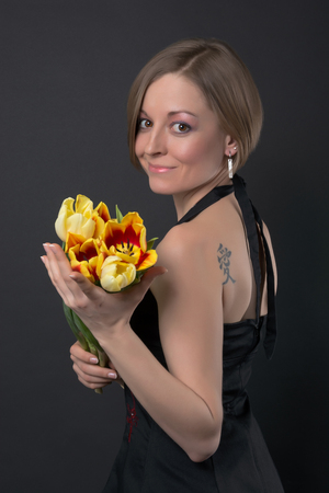 Girl in black dress, with a tattoo on her shoulder holding tulips in front of a black  photo
