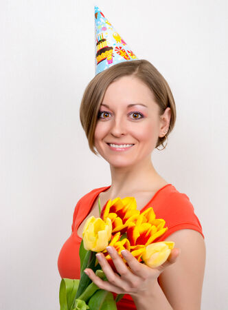 Woman celebrating birthday with tulips, party hat in front of a white background photo