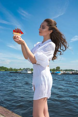 mujer mirando el horizonte: Chica tiene una peque�a nave con las velas rojas Modern Assol en el muelle de madera cerca del agua Foto de archivo