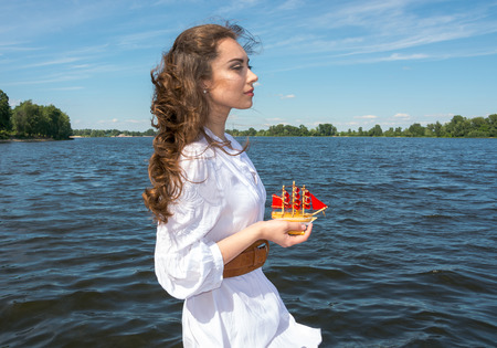 Girl holds a small ship with red sails   Modern Assol on the wooden pier near the water  photo