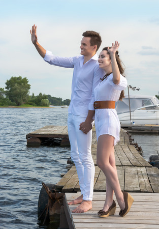 Guy holds the girl's hand on a wooden pier near the water. They wave their hands, behind them a lot of boats. Stock Photo - 29467413