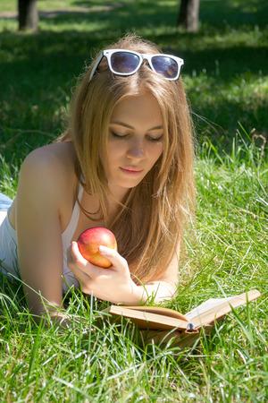 Girl holding a red apple and reading a book in a summer park on the grass photo