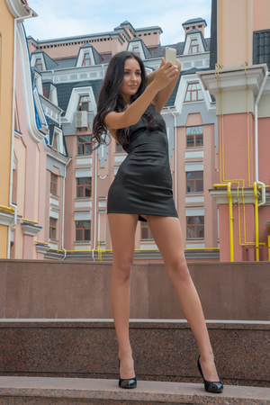 Beautiful woman taken picture of herself, selfie  Beautiful and slender girl talking on a cell phone on a city street  Model in little black dress in front of colorful buildings in a European city photo