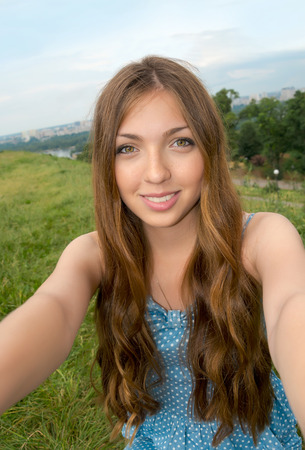 Beautiful girl taken picture of herself, selfie. Young woman with long hair photographed herself in front of the cityscape.