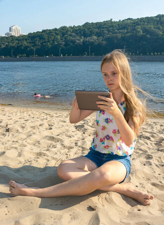 Girl in bright clothes on the beach with the tablet photo