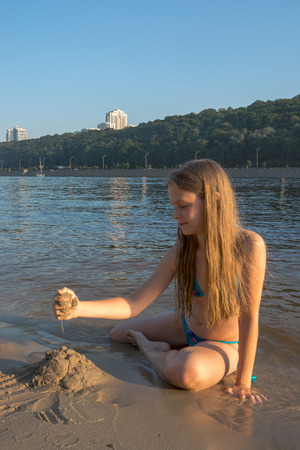 Girl builds a sandcastle on a beach by the river