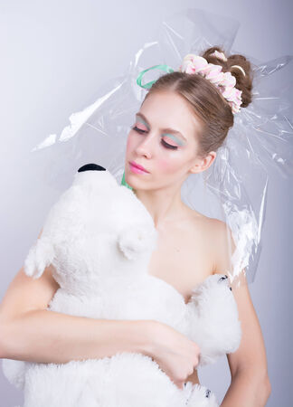 Girl with a toy bear in hands, beauty fantasy. Young woman with a gentle make-up and hairstyle, decorated with candy. Candy-girl package, candy makeup photo