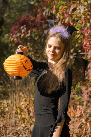 Girl in Halloween style. Girl dressed as a vampire bat and pumpkin in her hand on a background of autumn forest bokeh photo