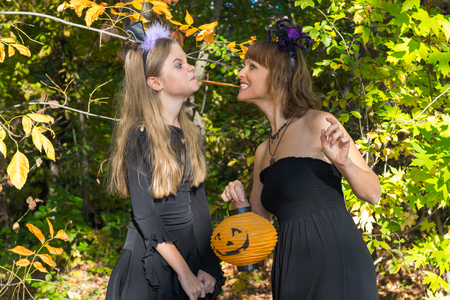 Mother and daughter in the style of Halloween. Girl and woman with a worm in the mouth, dressed as a vampire bat with a pumpkin in a hand on a background of autumn forest bokeh photo