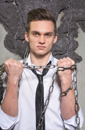 breaks: A man in a white shirt and tie breaks the chain Office worker breaks his chains Stock Photo