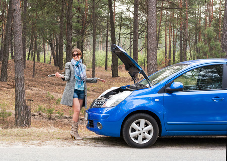 A girl is at a loss with the wrong wrench over the open car hood in the forest. photo