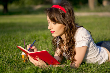 grass beautiful: Young girl with a notepad and pen in a summer park on the grass