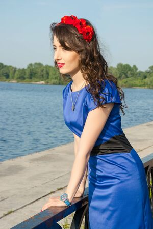 expects: A young woman in a wreath near a river. Model in blue dress near a river in the summer.
