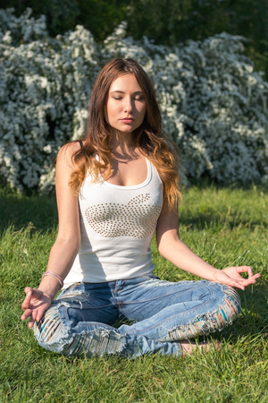 meditates: Young woman practices yoga and meditates in a park