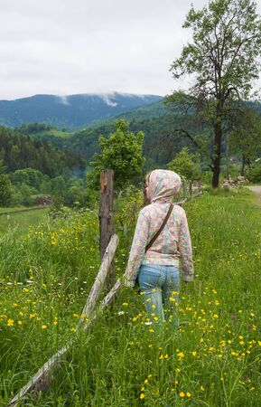 old fence: Teenage girl looking into the distance near an old fence and a railroad in the mountains