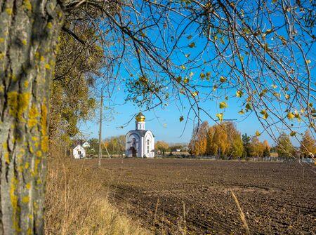 plowed field: Church on the edge of plowed field. Autumn landscape Stock Photo