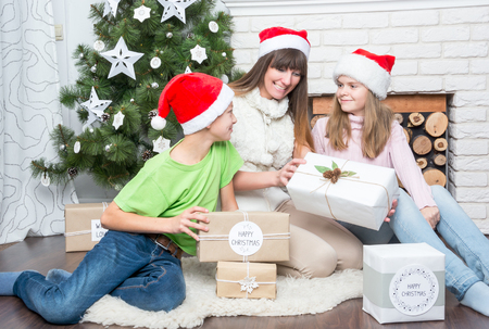 considers: Mom with kids considers gifts near a Christmas tree