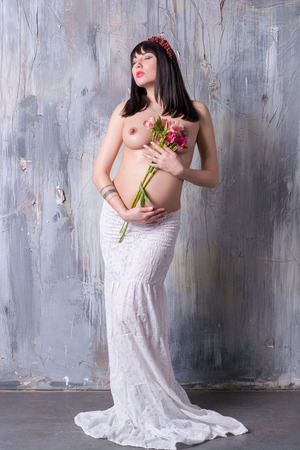 Young pregnant woman topless with flowers near the breast, feminine image of the expectant mother.