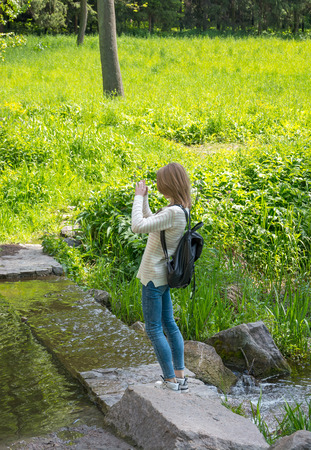 Girl takes pictures landscape on cell phone. Young girl doing selfie in the park Stock Photo