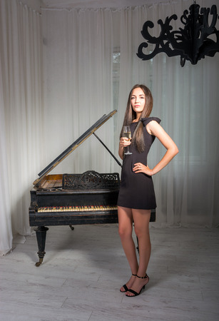 Girl in a cocktail dress near the retro piano with a glass of wine