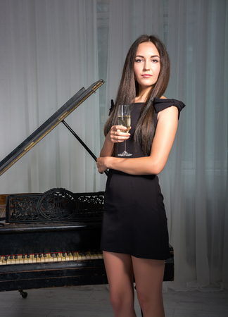 supercilious: Girl in a cocktail dress near the retro piano with a glass of wine