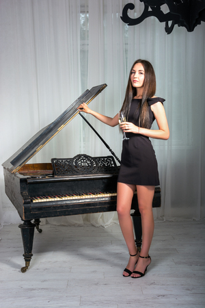 pretty dress: Girl in a cocktail dress near the retro piano with a glass of wine