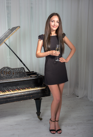 pretty brunette woman: Girl in a cocktail dress near the piano with a glass of wine