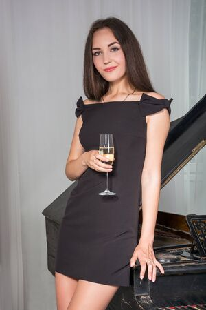 cocktail dress: Girl in a cocktail dress near the retro piano with a glass of wine