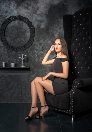 pretty brunette woman: Girl in a short black dress sitting in a high chair in front of a dark background