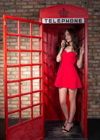 Jonge vrouw in een korte rode jurk praten aan de telefoon in de oude telefooncel