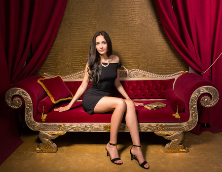 Young beautiful woman in black little dress sitting on a red velvet sofa in the interior in gold