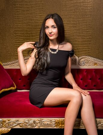 velvet dress: Young beautiful woman in black little dress sitting on a red velvet sofa in the interior in gold