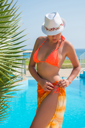 Beautiful sexy woman in a hat, in a orange swimsuit, chiffon pareo near a palm tree. Stock Photo