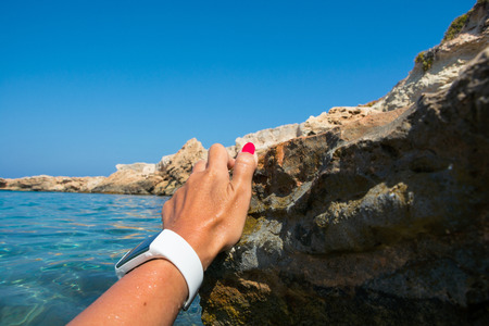 Female hand in a fitness tracker in azure seawater. Girl swims in the sports bracelet. Stock Photo