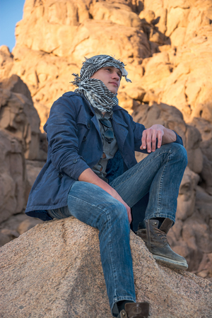 sinai desert: Young man in a keffiyeh sitting on a rock in the desert Stock Photo