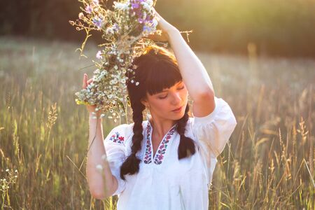A young woman in a long white embroidered shirt puts on a wreath of wild flowers in a meadow at sunset. Girl in ancient national clothes. Stock Photo