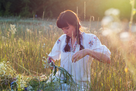 A young woman in a long white embroidered shirt weaves a wreath of wild flowers in a meadow at sunset. Girl in ancient national clothes. Light effect from the suns rays Stock Photo