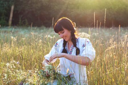 長い白い刺繍シャツの若い女性は、日没で牧草地の野生の花の花輪を編みます。古代国家の服の女の子。太陽の光から光の効果