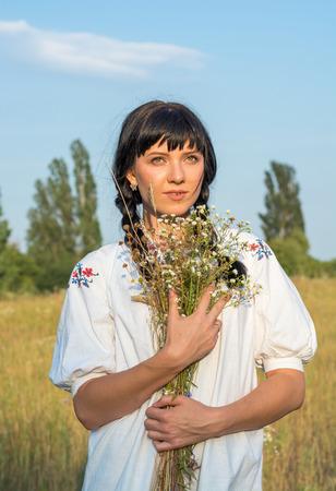 長い白い刺繍シャツの若い女性は、夕暮れ時、草原で手に花の花束を保持します。古代国家の服の女の子。