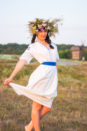 spit: A young woman in a long white embroidered shirt and in a wreath of wild flowers stands in the field at sunset in the background an ancient flour mill. Girl in ancient national clothes.