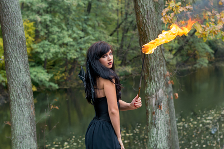 Young brunette women with Halloween witch makeup stands with a torch in a black dress standing in a black dress before an autumn lake